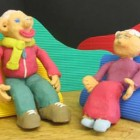 Two plasticine models of people sitting on chairs talking to eachother - a still from the animation